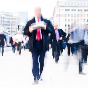 תמונת אילוסטרציה מטושטשת של איש הולך ברחוב קורא עיתון